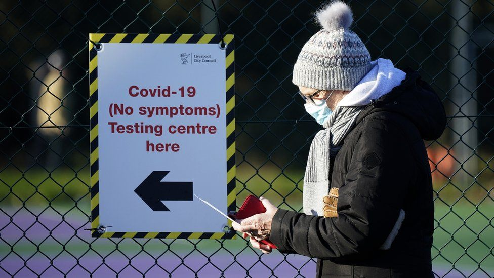 Members of the public queue at a mass Covid-19 testing site in the Liverpool Tennis centre at Wavertree Sports Park on January 05, 2021 in Liverpool, United Kingdom