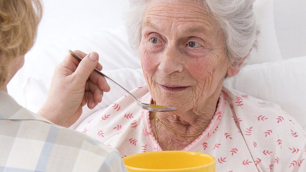 Old woman being fed