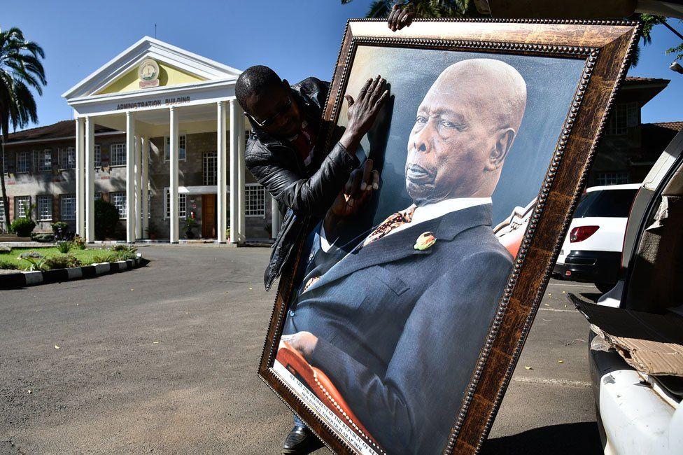 A man holding a portrait of the late former President of Kenya, Daniel arap Moi