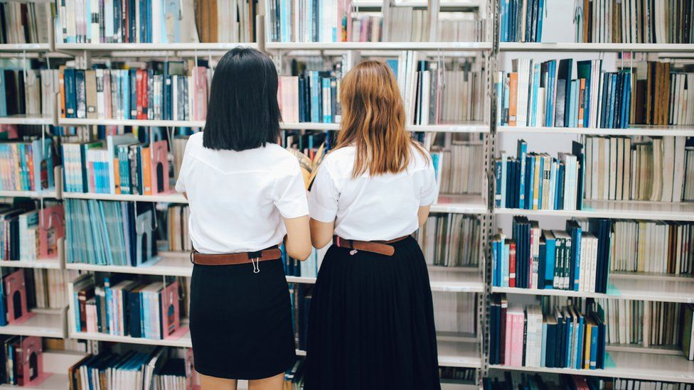 Two female students searching for books in a library - stock photo
