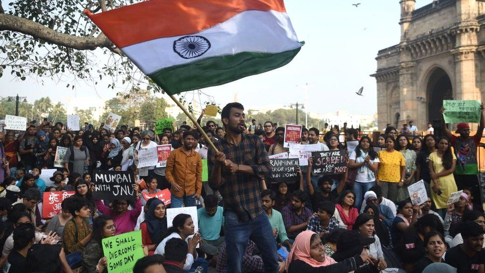 Protesters and students shout slogans and hold Indian flags as they protest against the violent clashes