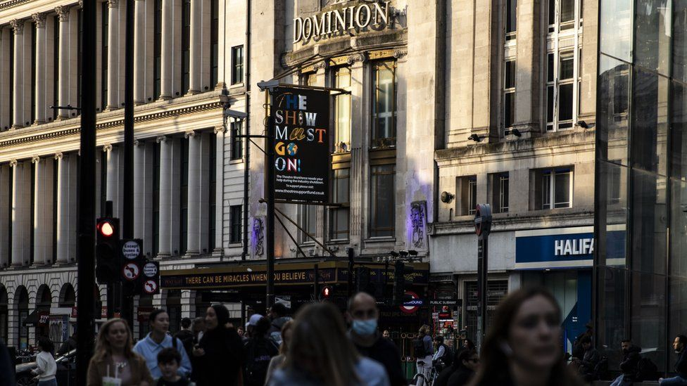 Crowds in front of the Dominion Theatre with a sign saying The Show Must Go On
