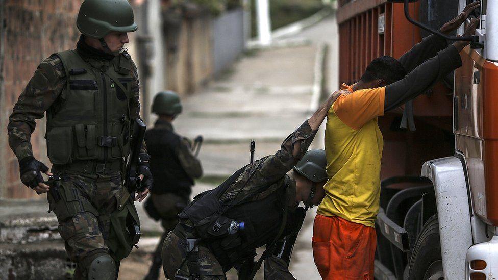 Law enforcement officers search a man in Niteroi, in the metropolitan region of Rio de Janeiro, Brazil, 16 August 2017