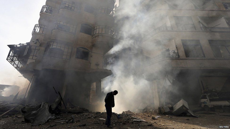 A man (with head bowed) walks in front of a burning building after a Syrian air force strike in Ain Tarma neighbourhood of Damascus January 27 2013