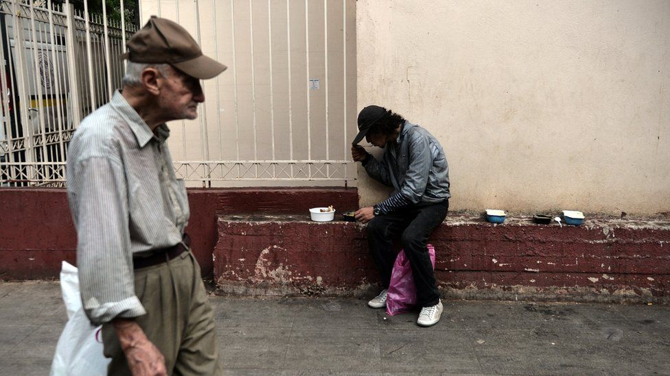 A man eats after he received food offered by the Greek church in central Athens