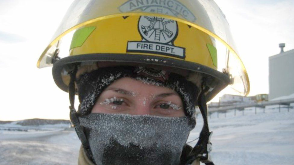 A woman in a yellow helmet with 'Antarctic Fire Dept.' written on it. She is wearing a scarf over her nose, covered in ice.