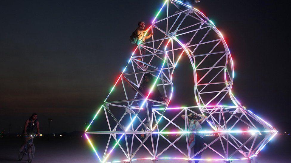 Festival goers climb an art installation at Burning Man 2013