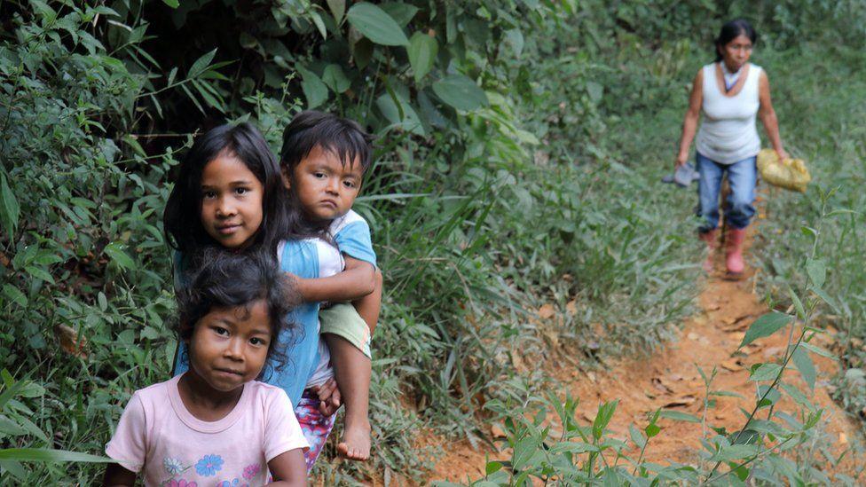 Irene Guasiruma walks with children along a path