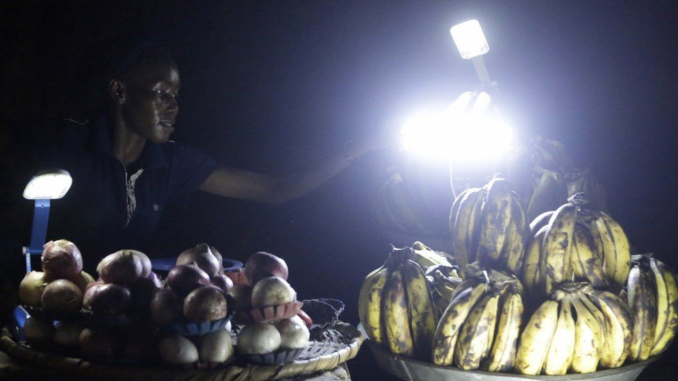 A plantain and onion vendor plies her wares by lantern light in Lagos, Nigeria - Monday 20 February 2017