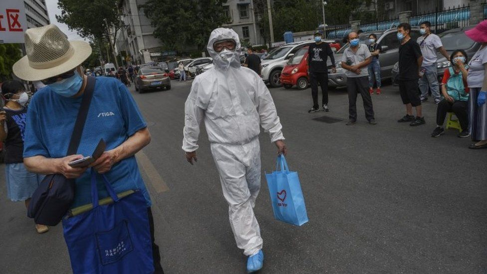 A health worker in Beijing holds a blue carrier bag