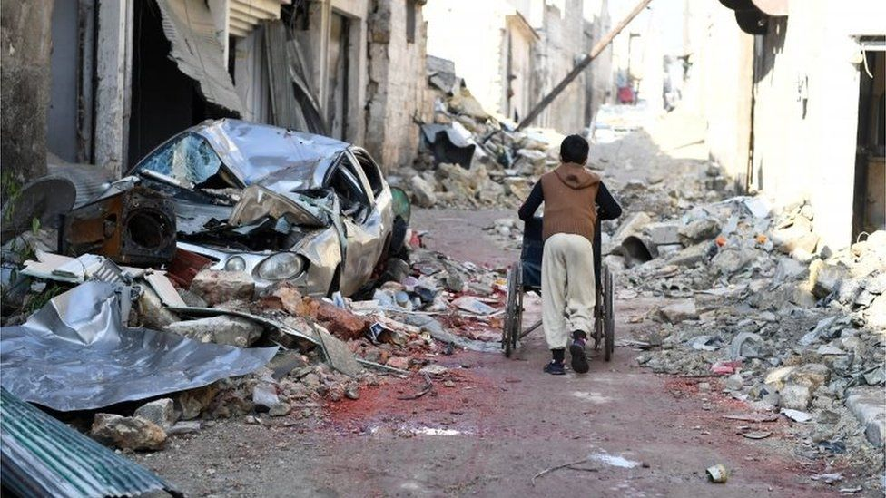 A boy pushes a wheelchair along a damaged street in the east Aleppo neighbourhood of al-Mashatiyeh, Syria, in this handout picture provided by UNHCR on 4 January 2017