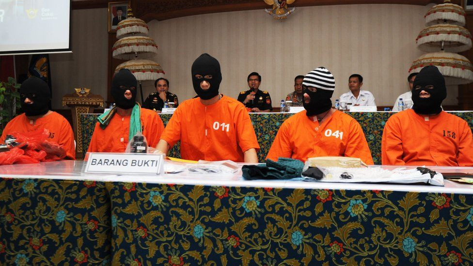 Five men who were arrested in Indonesia are paraded at a press conference