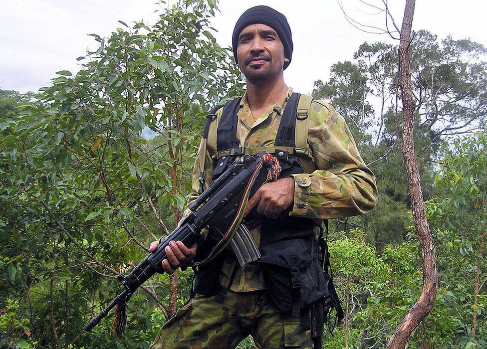 The fugitive rebel leader, Major Alfredo Reinado, poses for photographers, wearing Australian military fatigues and holding a weapon, in the forest in Same, 50 kilometres (30 miles) south of the capital Dili, 12 March 2007.