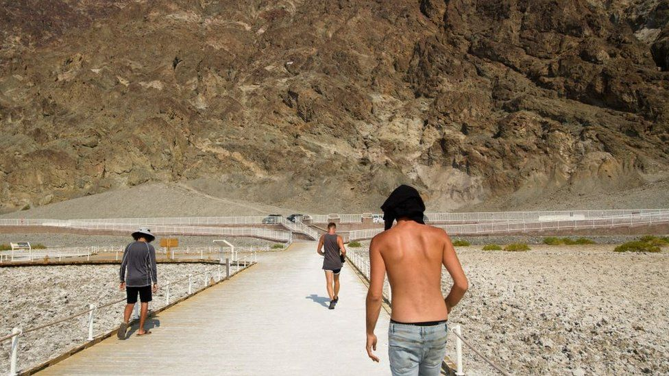 Visitors walk by the salt flats of Badwater Basin inside Death Valley National Park