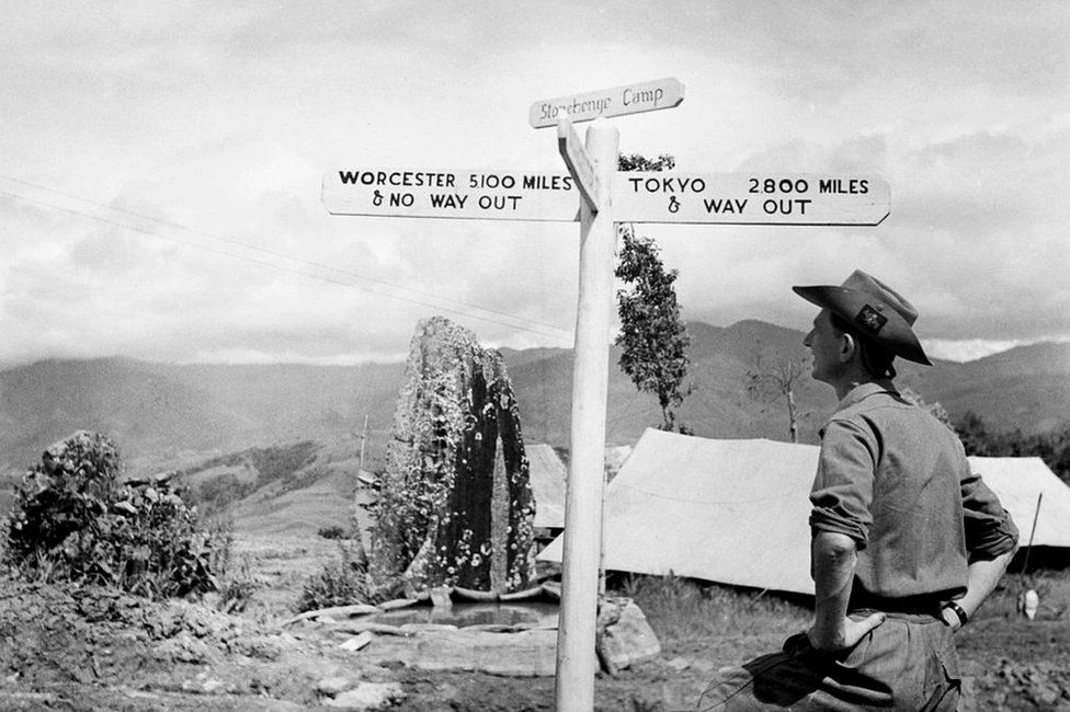 The British Army In Burma 1944 - a member of the Worcestershire Yeomanry views an amusing road sign beside an ancient standing stone at 'Stonehenge Camp' on the Imphal to Kohima road.