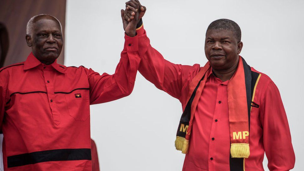 Angolan President and The People's Movement for the Liberation of Angola President Jose Eduardo dos Santos and MPLA candidate to the presidency Joao Lourenco hold hands during the closing campaign rally in Luanda, on August 19, 2017.