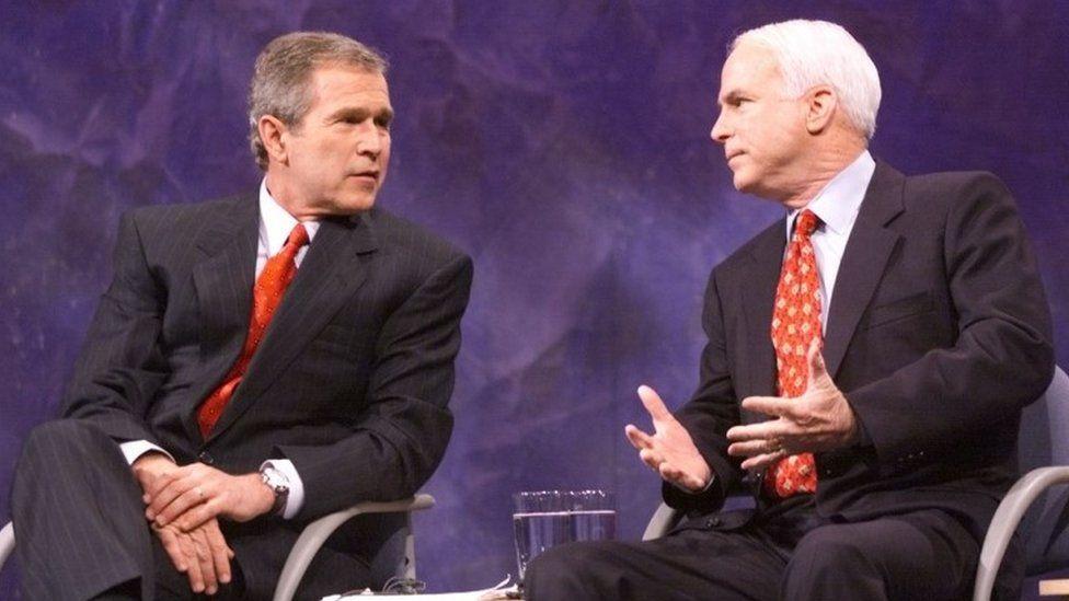 Republican US presidential candidates Texas Governor George W. Bush (L) and Senator John McCain of Arizona talk before the start of the Iowa debate
