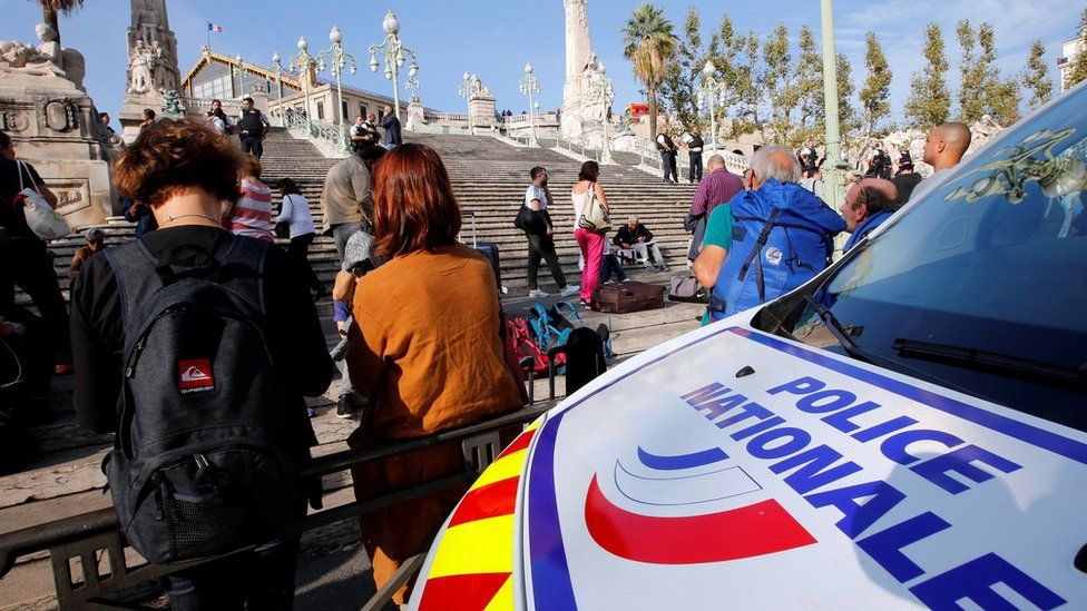 Travellers gather at the steps outside Marseille train station, in front of a police van (1 October 2017)