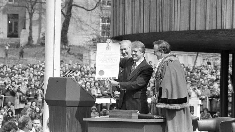 President Carter holds a scroll making him an honorary freeman of the city of Newcastle, 6 May 1977