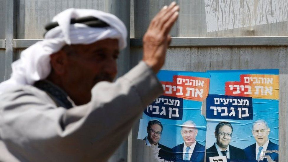 Palestinian gestures next to Israeli election posters in Hebron (07/09/19)