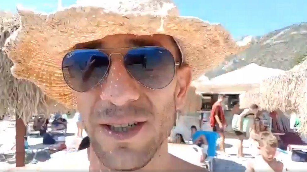 Adam Catzavelos on a beach
