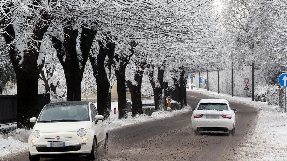 Cars travel through an area covered in ice and snow in freezing temperatures in Como, northern Italy, 13 January