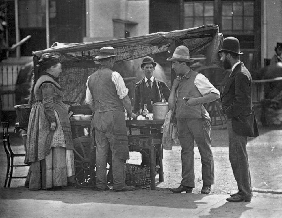 A Victorian shellfish stall holder selling oysters and whelks.