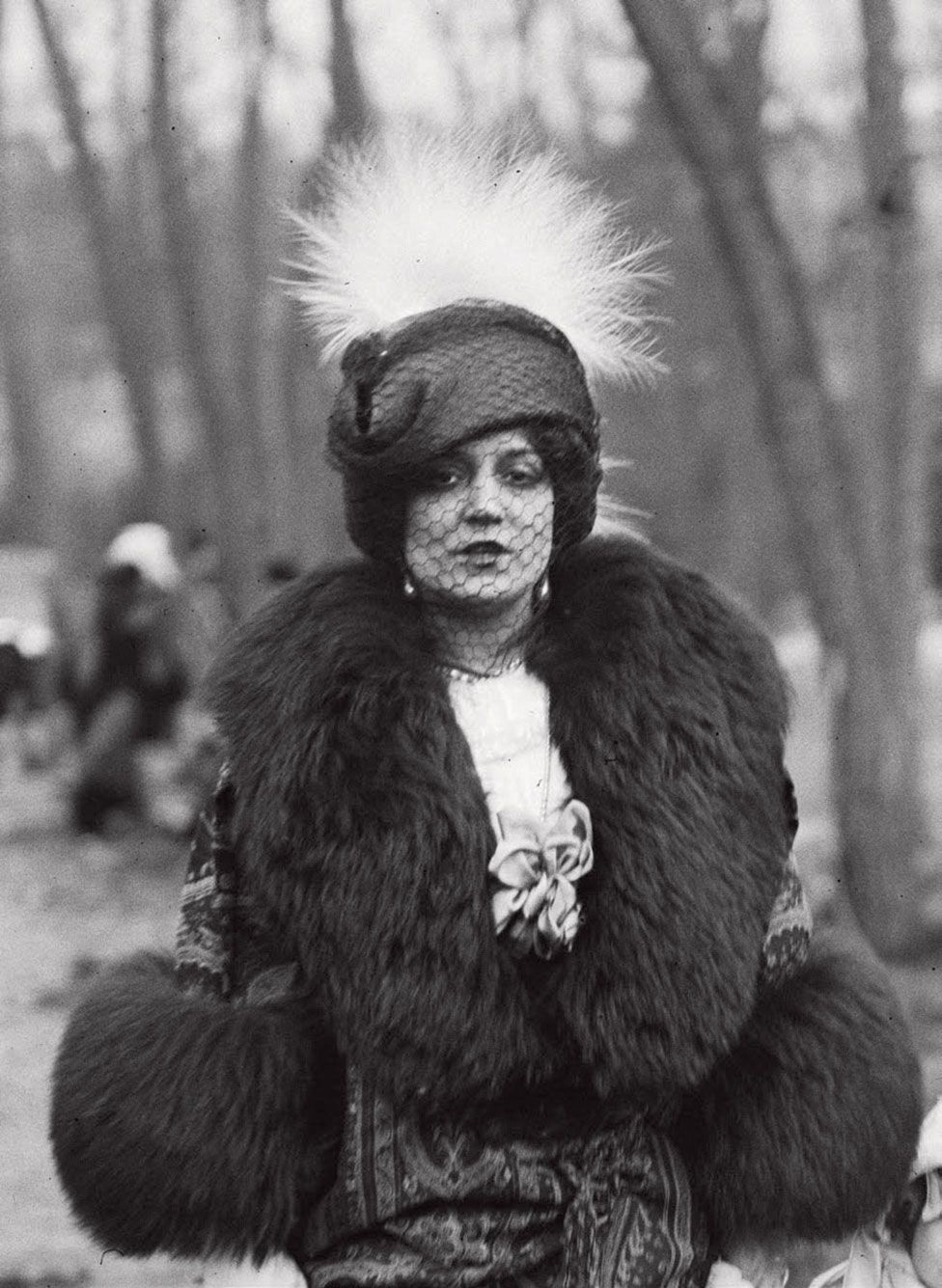 A portrait of a woman in a park wearing an elaborate hat, face veil and thick fur coat