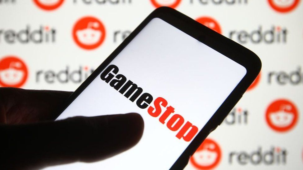 GameStop logo on a phone against a background of Reddit logos.