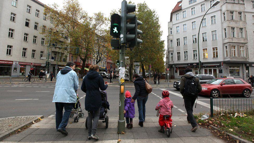 A group of parents and children cross the street in the former East German neighbourhood of Prenzlauer Berg
