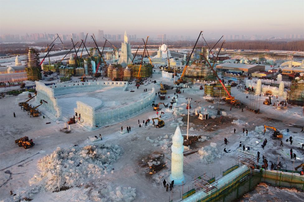 Workers build ice structures at the site of the Harbin International Ice and Snow Festival