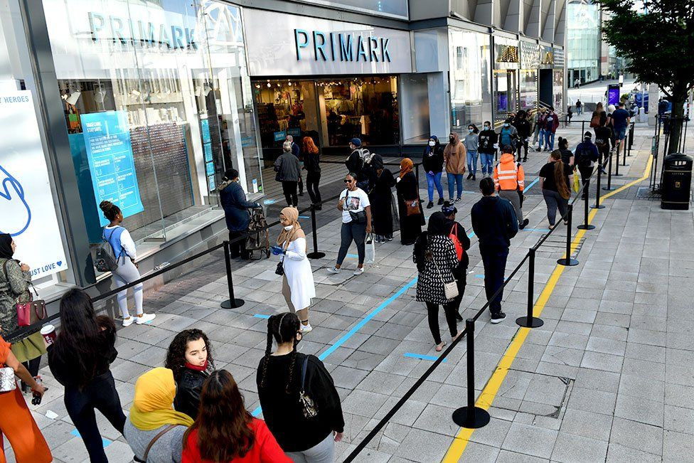 Customers queue to enter a Primark store