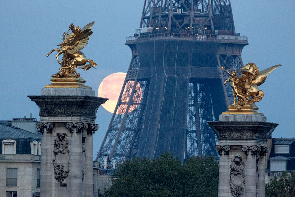 The pink supermoon seen against the Eiffel Tower and the Pegasus Held By Fame statues on the Pont Alexandre III bridge in Paris, France