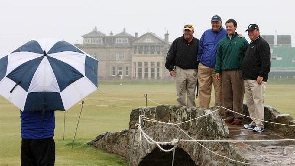 US tourists pose for a picture on the Swilcan Bridge at the famous St Andrews course in Scotland