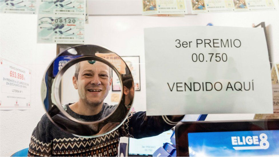 """Juan Carlos De Quintana, owner of the lottery administration number 1 in Vitoria celebrates selling the number 00750, awarded the third prize in """"El Gordo""""."""