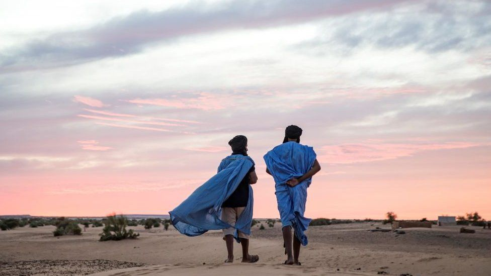 Two men walk in the desert of Guelb El Jmêl, in the eastern Mauritania on November 21, 2018.
