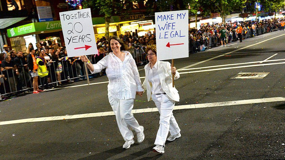 A couple carrying placards at the Mardi Gras in 2013
