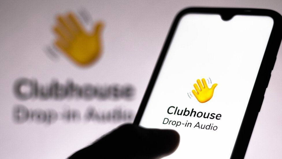 The Clubhouse logo is seen on a smartphone being held by a hand in this close-up shot