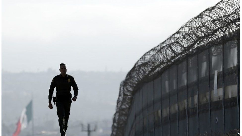 US border official patrolling the fence separating Tijuana in Mexico and San Diego in San Diego