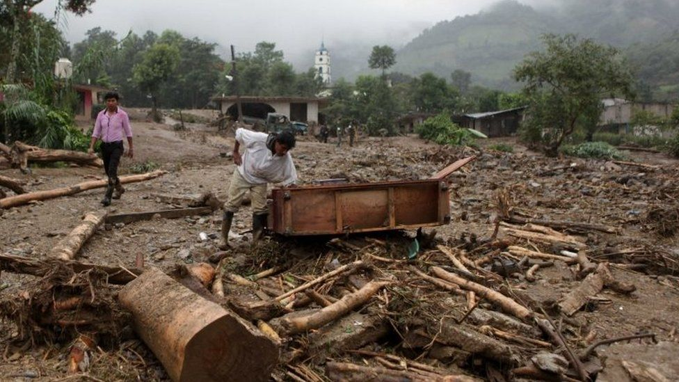 A man inspects furniture that was dragged by a mudslide in Xaltepec, on the mountainous north of Puebla state, Mexico, Sunday, Aug. 7, 2016.
