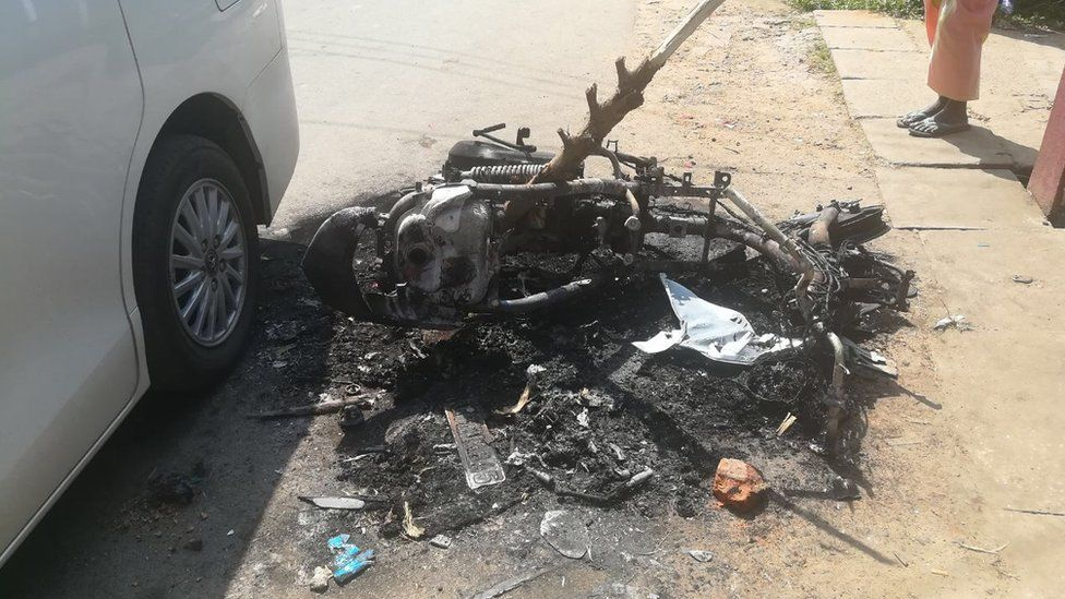 A motorbike frame is abandoned in the street after it was burned in street clashes in Galle province, Sri Lanka