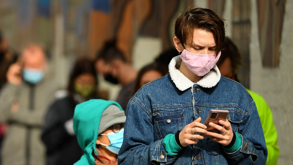 A young man wearing a mask checks his phone while queueing for a Covid test in Melbourne