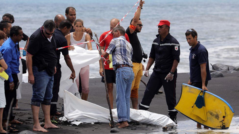 Police, firefighters and others stand next to the body of a body-boarder killed by a shark, covered by a white cloth, on 21 February 2017 on a beach in Saint-Andre, on the French island of Reunion in the Indian Ocean