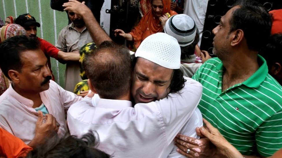 Brother of Amjad Sabri being comforted