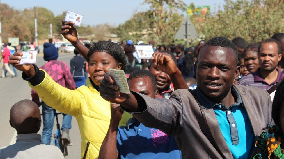 voters hold out id cards in lusaka