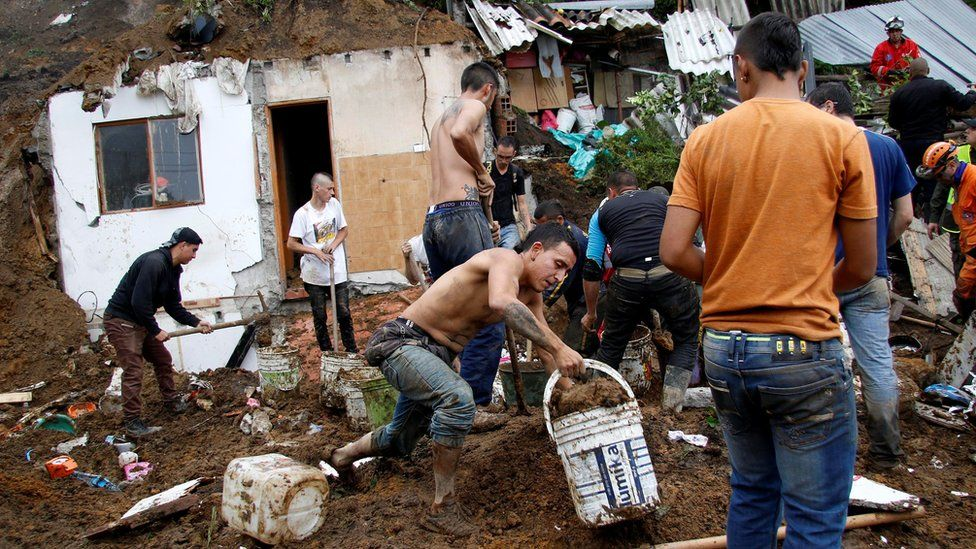 People and rescue agencies look for bodies in a destroyed area after mudslides, caused by heavy rains leading several rivers to overflow, pushing sediment and rocks into buildings and roads, in Manizales