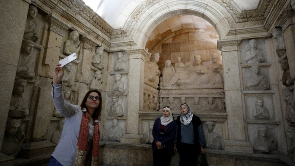 Three women take a selfie during its re-opening