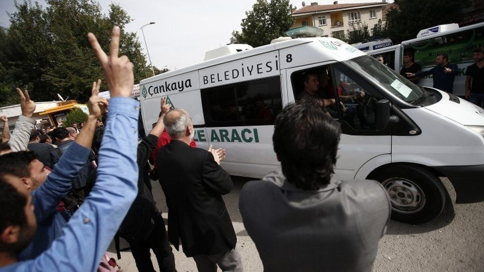 Mourners display the V-sign and applaud as an ambulance carrying a victim of Saturdays bombing attack leaves a hospital's morgue for a funeral procession, in Ankara (11 October 2015)