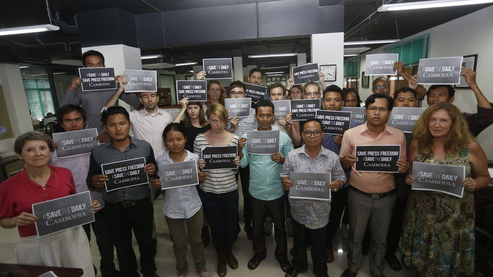 Cambodia Daily staff hold placards reading #SaveTheDaily