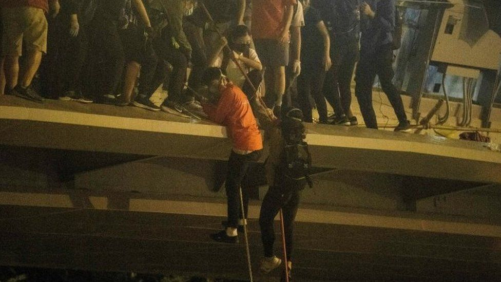 Protesters lower themselves down a rope from a bridge to a highway to escape Polytechnic University campus